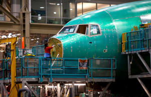 An employee works on the nose of a Boeing Co. 777 airplane at the company's faci...