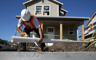 A worker cuts a piece of pipe as he builds a new home on January 21, 2015 in Pet...