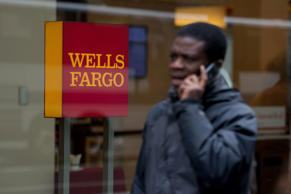 A pedestrian talks on the phone while passing in front of a Wells Fargo & Co...