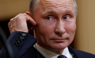 Russian President Vladimir Putin listens as U.S. President Donald Trump speaks d...