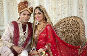 Indian bride and groom in traditional wedding dress sitting on a couch