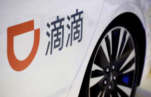 The company logo of the Didi ride hailing app is seen on a car door at the IEEV ...