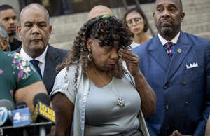Gwen Carr, mother of the late Eric Garner, wipes away tears after speaking to th...