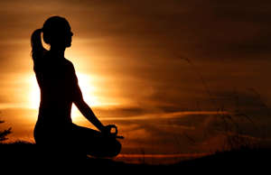 Silhouette of a woman practicing yoga against the light of the evening sun. Lotu...