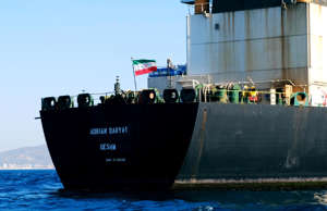 A crew member raises the Iranian flag on Iranian oil tanker Adrian Darya 1, prev...