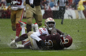 Rain water splashes as San Francisco 49ers cornerback Jimmie Ward (20) tackles W...