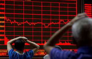 Investors monitor a display showing the Shanghai Composite Index at a brokerage ...