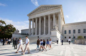 FILE - In this Oct. 14, 2014, file photo, people walk outside the Supreme Court ...