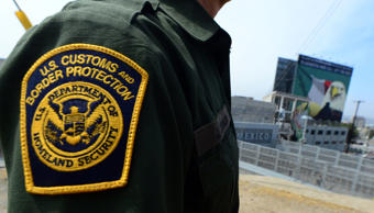 File photo of a US Border Patrol agent standing near a crossing to Mexico at the...