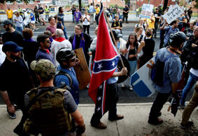 A white supremacists carries the Confederate flag as he walks past counter demon...