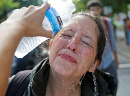 A counter demonstrator gets a splash of water after being hit by pepper spray at...
