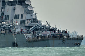 The guided-missile destroyer USS John S. McCain, with a hole on its portside aft...