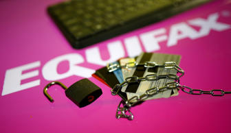 Credit cards, a chain and an open padlock is seen in front of displayed Equifax ...