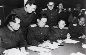 Communist representatives sign the agreement for the neutral zone, reached throu...