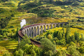 Glenfinnan Railway Viaduct in Scotland with the Jacobite steam train passing ove...