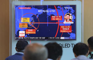 People watch a TV news program reporting a North Korea's missile launch, at the ...