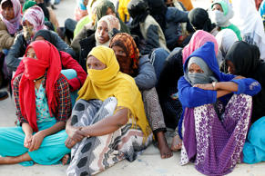 Migrants sit at a naval base after being rescued by Libyan coast guards in Tripo...