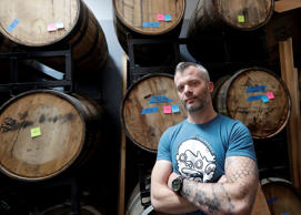 Jim Furman, CEO of Black Hammer Brewing, poses for photos in front of barrels in...
