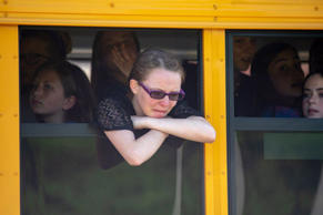Evacuated middle school students wait on a bus outside Noblesville High School a...