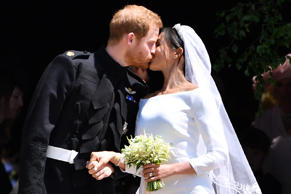 Prince Harry and Meghan Markle kiss on the steps of St George's Chapel in Windso...
