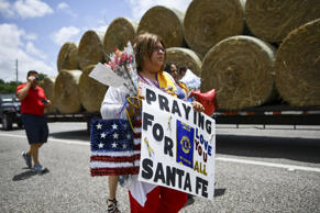 Residents bring memorial items to Santa Fe High School on May 19, in Santa Fe, T...