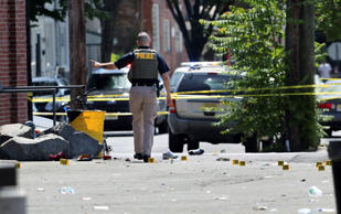 A police officer stands in a lot near evidence markers outside the warehouse bui...