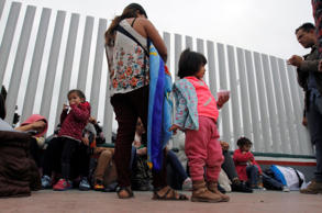 Migrant families wait to enter the United States border and customs facility to ...
