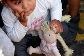 A member of a migrant family from Mexico, fleeing from violence, holds her doll ...