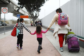 A migrant mother walks with her two daughters on their way to the port of entry ...