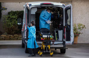 Medics clean their equipment after transporting a patient into Life Care Center ...