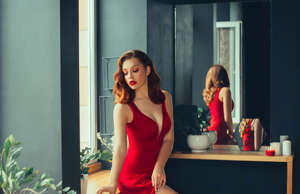 hot young adult, proud and domineering woman dressed in a long scarlet red long ...