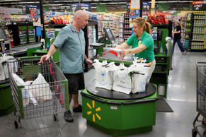A customer speaks to the cashier as he checks out at a Walmart Neighborhood Mark...