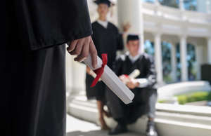 College student at graduation holding a diploma
