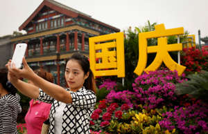A Chinese tourist takes selfie at Tiananmen Square, Beijing during the weeklong ...