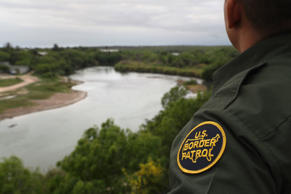 A U.S. Border Patrol agent scans the U.S.-Mexico border while on a bluff overloo...
