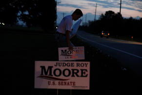 Mason Green, a supporter of U.S. Senate candidate Roy Moore, posts campaign sign...