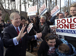 Democratic candidate Doug Jones greets supporters after casting his ballot Tuesd...
