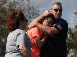 A family prays outside Marjory Stoneman Douglas High School in Parkland, Fla., S...