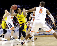 <p>UMBC's Jairus Lyles (10) drives past Virginia's Devon Hall (0) during the fir...