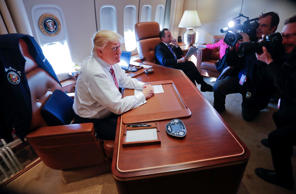 President Donald Trump sits at his desk on Air Force One upon arrival at Andrews...