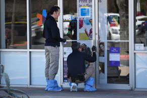 Law enforcement personnel are seen gathering evidence outside a FedEx Store whic...