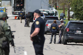 Officials investigate the scene where a suspect in a series of bombing attacks i...