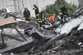 Rescuers work in the rubble after a highway bridge collapsed in Genoa, Italy, Au...