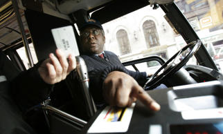 New York City bus driver David Smith points out how to use the fare system to a ...