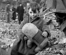 Abandoned boy holding a stuffed toy animal amid ruins following German aerial bo...