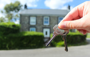 Close up of keys to a house in the background