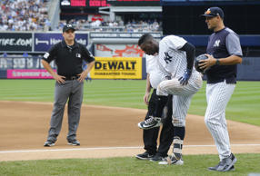 The Yankees' Didi Gregorius goes down after a collision with Blue Jays first bas...