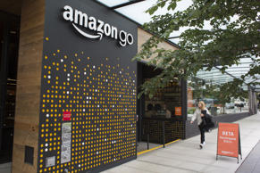 A woman walks past the Amazon Go grocery store at the Amazon corporate headquart...