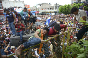 Thousands of Honduran migrants rush across the border towards Mexico, in Tecun U...