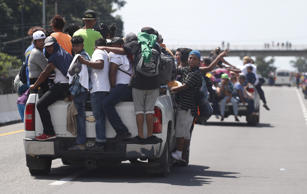 Central American migrants making their way to the U.S. in a large caravan cling ...